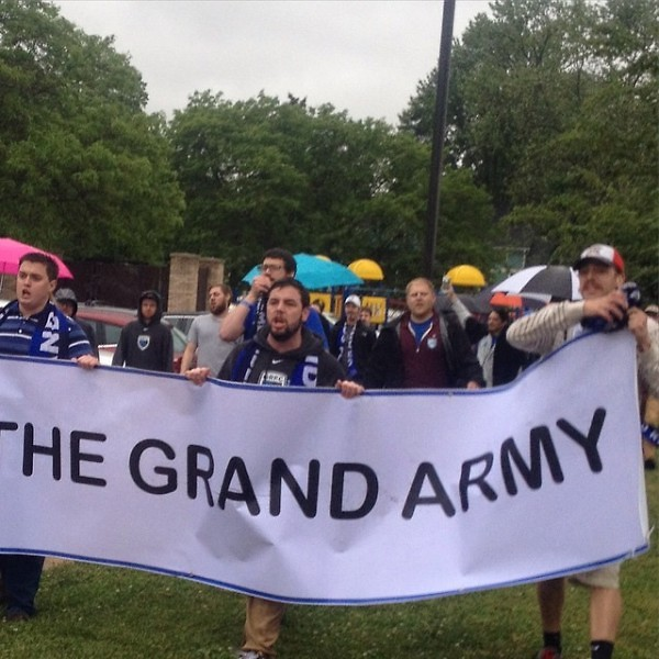 Members of the Grand Army, the fan support group of Grand Rapids Football Club, march to a game at Houseman Field.