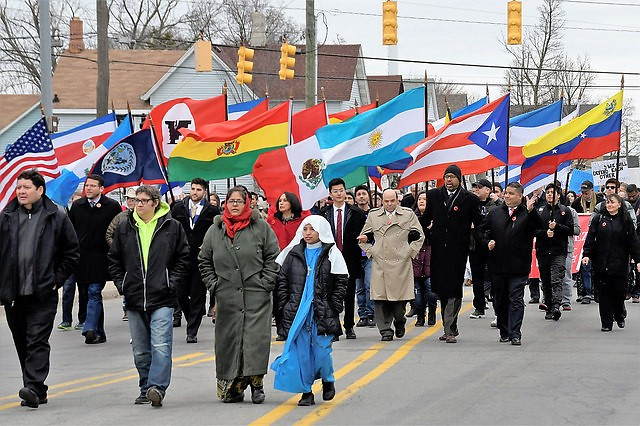 Community members and leader march in honor of César E. Chávez