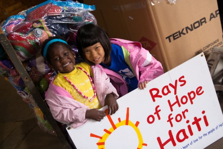Two volunteers donate supplies to their young Haitian peers.