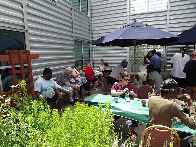 Residents gather in the courtyard of their building to network and complete the Heartside Resident Satisfaction Survey.