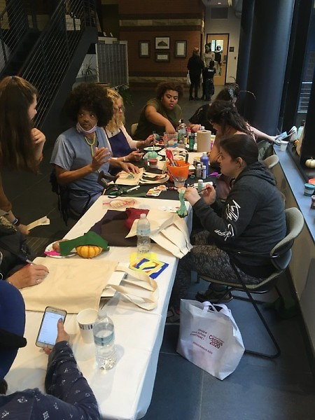 Residents gather around a community table to make fall-themed artwork