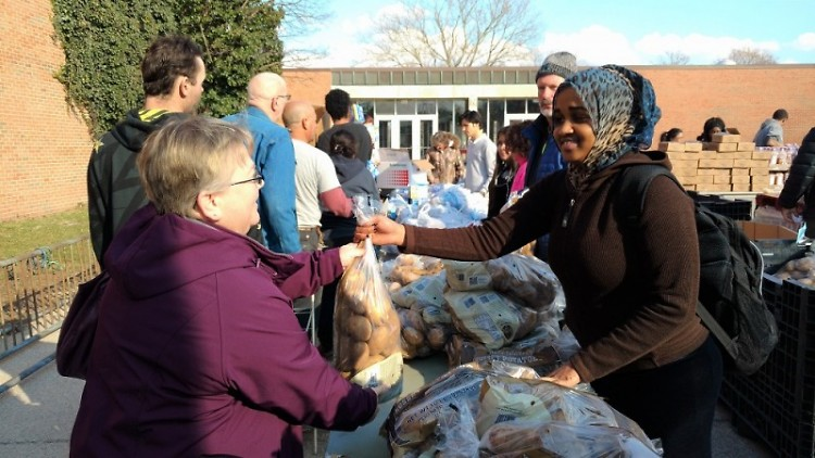 Senior Amina Abdullahi gives a bag of potatoes to a client at Union's Feb. 27 Mobile Pantry.