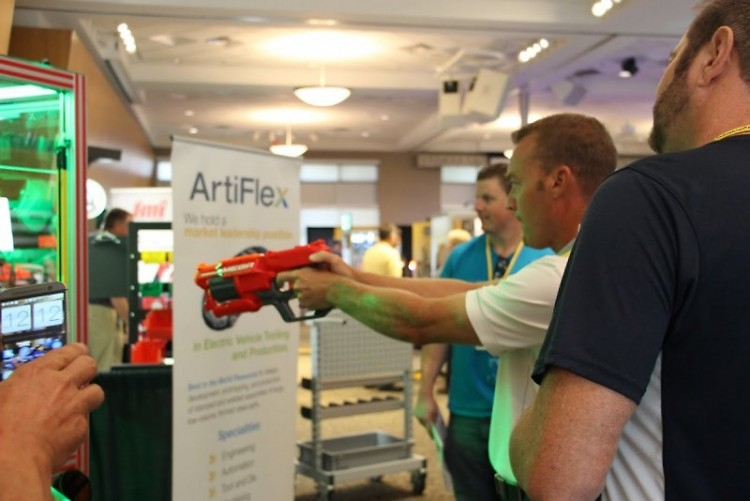 Expo attendee tests sharpshooting skills at ArtiFlex Automation game that uses industrial robot to pick out prizes.