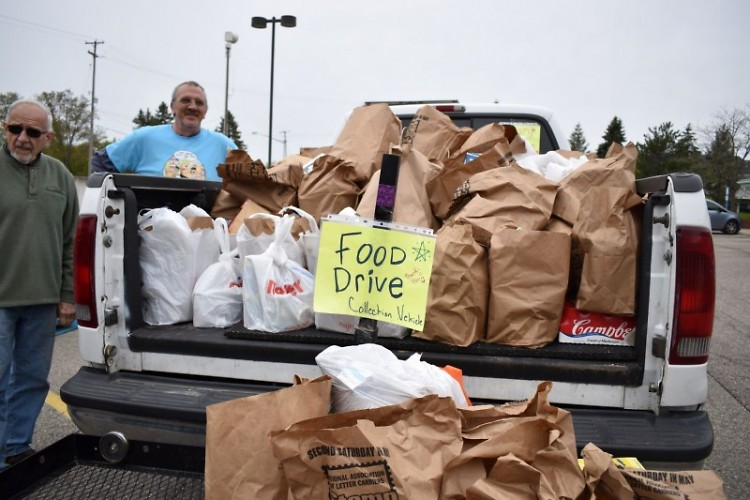 Volunteers receive a truck full of donations arriving at a Grand Rapids post office.