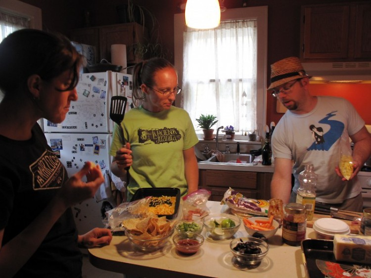 Amanda Narvaes (left) and Josh Dunigan (right) survey their spread with upstairs neighbor Jennifer Beahan (center).