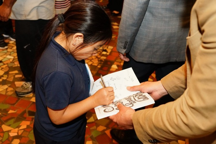 A young author signs a book during the Bloom Cherry Bloom Tree celebration