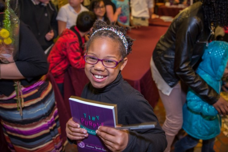 CYC student author with copy of The Book of Explosions IV: Tiny Purple Thunderlights
