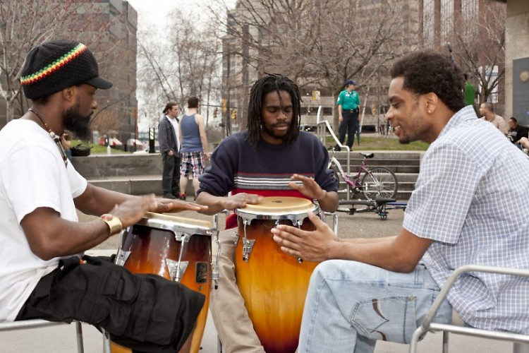 Kamau Re'xi, Manchurian Bell, and Herb Wise play bongos in Rosa Parks Circle