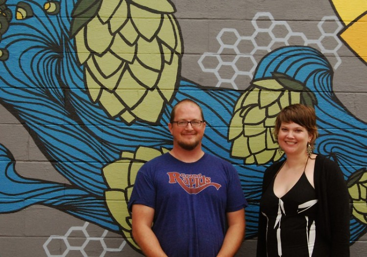 Barry VanDyke and Heather VanDyke-Titus stand in front of the mural painted on the outside of Harmony Brewing Company