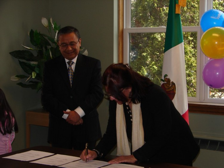 Sr. Vicente Sanchez of the Mexican Consulate and Co-Chair Zulema Moret sign the Plaza Comunitaria contract