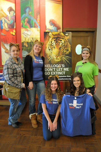 A group of volunteers and participants gather around a sign pleading Kellogg's to help save the Sumatran Tiger.