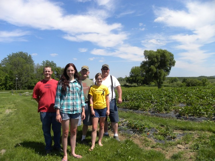 Roy and Aaron Johnson with family friends, employee and strawberries