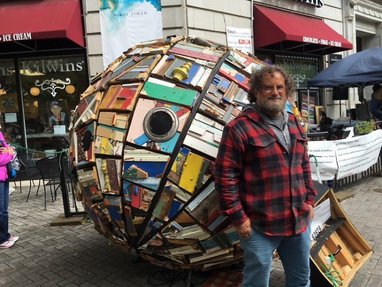 "Artist Loren Naji stands outside of his sculpture ""Emoh,"" which represents society's ""backwards"" approach to homelessness."
