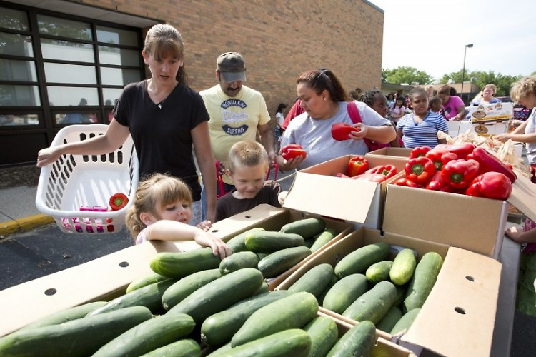 Sarah Crandall and her children gather groceries at a Feeding America West Michigan distribution in July.