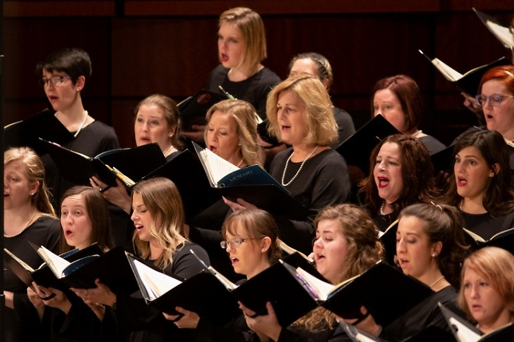 Mary Tuuk (center) who sings soprano with the Grand Rapids Symphony Chorus has been named President and CEO of the orchestra