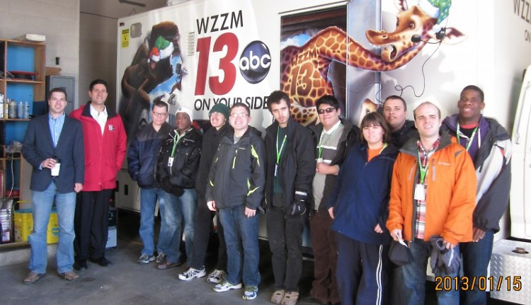 Dan Harland and Aaron Ofseyer pose with the HC1 students in front of the WZZM news vehicle entered into ArtPrize.