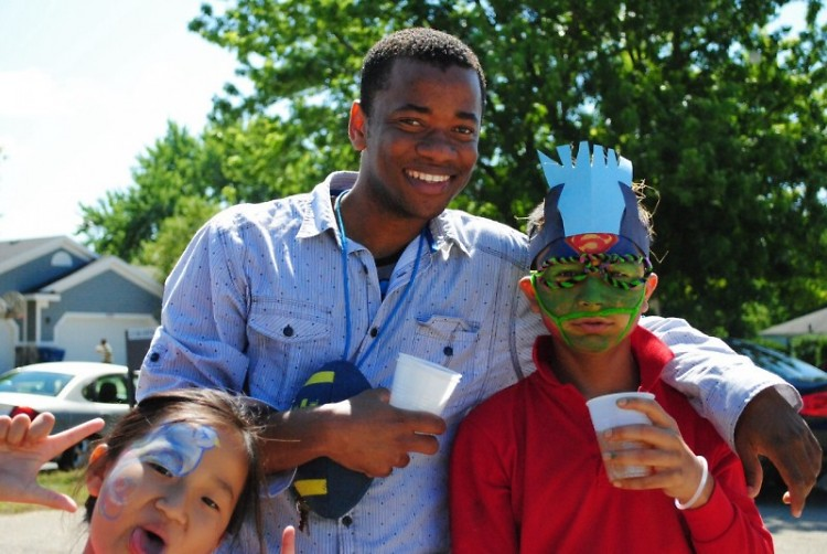 Abdi Osman, a Student Support Coordinator with two students during Refugee Education Center's summer programming.