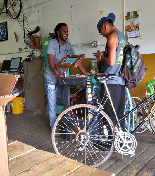 Martel Posey helping a patron after servicing their bike