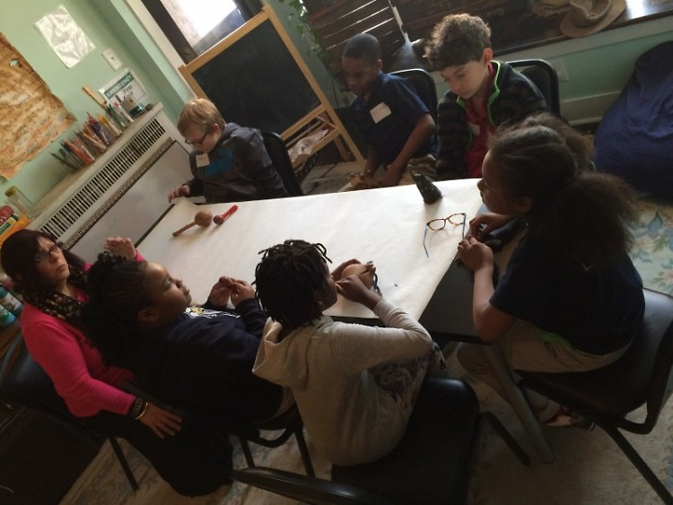 Young writers exploring artifacts for inspiration at the Creative Youth Center