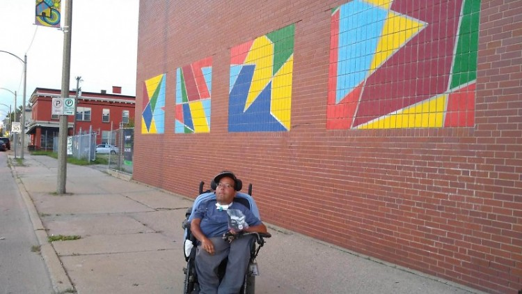 Javier Torres, Cultura Collective artist in front of his mural.