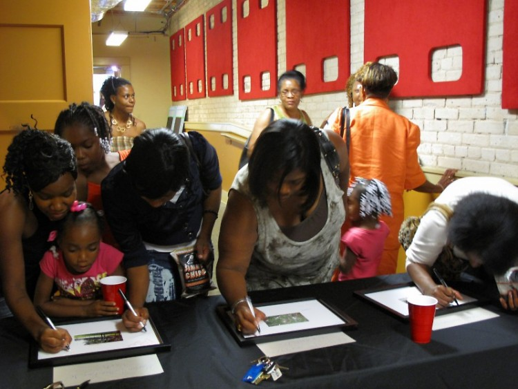 Participants scribble their hopes and wishes on three photos of Southtown taken by youth.