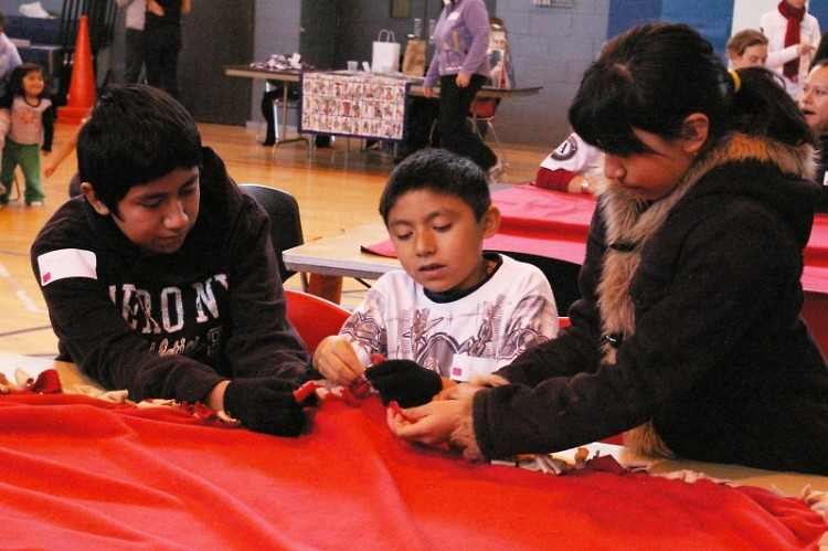 Children in the Schools of Hope Family Literacy Program work together to make a comfort blanket for house fire victims.
