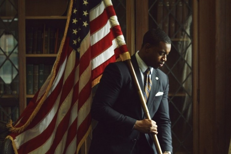 Leighton Watson posing with the American flag at Howard University