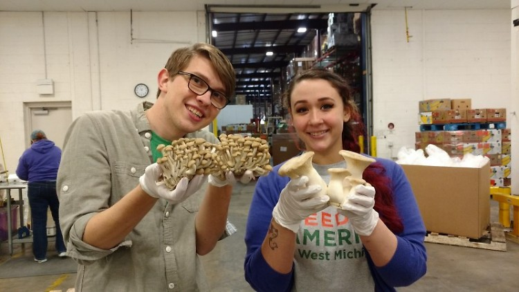 Feeding America West Michigan staff members Josiah Kinney and Francesca Almonte display mushrooms donated by GMI.