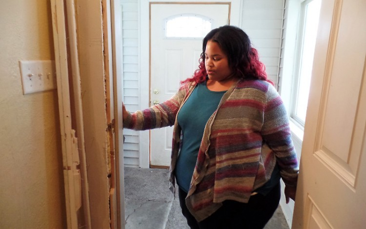 Lisa Wilkerson shows the damage to door entering her living area.