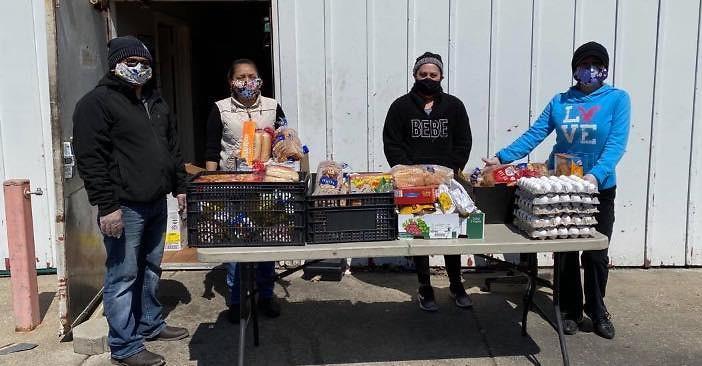 Miembros de Grand Rapids Area Mutual Aid Network (GRAMAN) distribuye alimentos a familias locales necesitadas.
