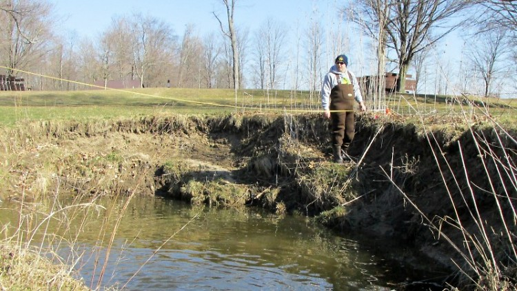 Standing on a half-slumped bank, a teacher from a GR middle school helps us measure a section of Plaster Creek at Shadyside Park