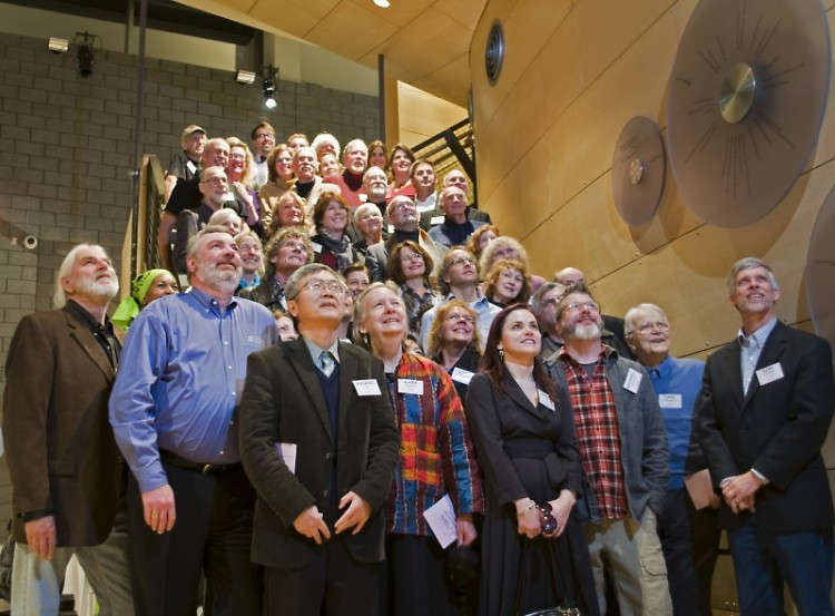 Artists look upward for a group photo ten years in the making.