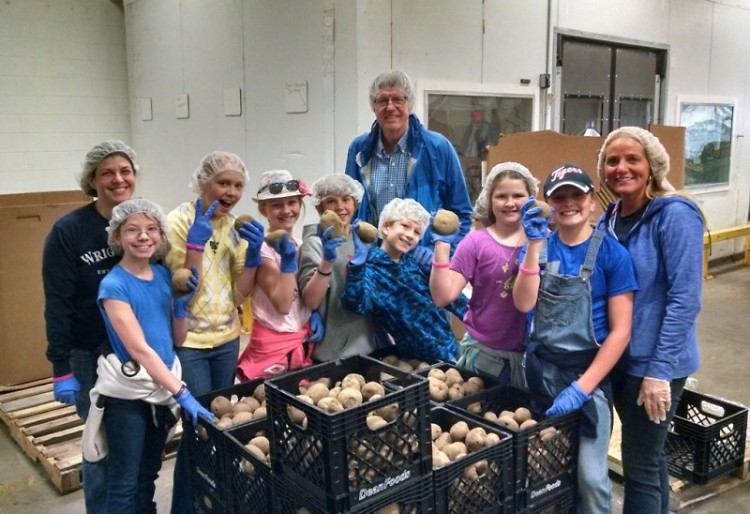 Fifth-grade students pack food at Feeding America West Michigan, April 22.