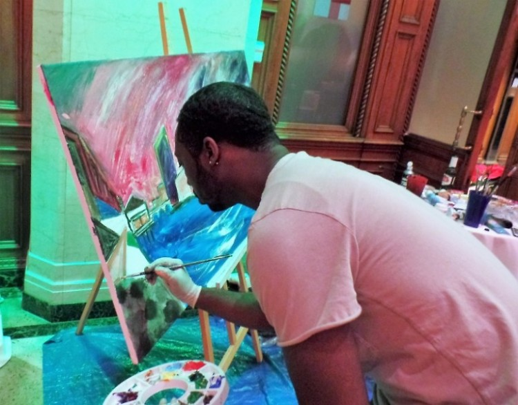 Artist J.A. Medcalf creates a colorful cityscape of Grand Rapids during the Race Together fundraiser