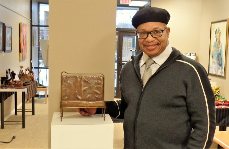 GRAAMA director George Bayard III stands with a replica of the Rosa Parks bus bench.