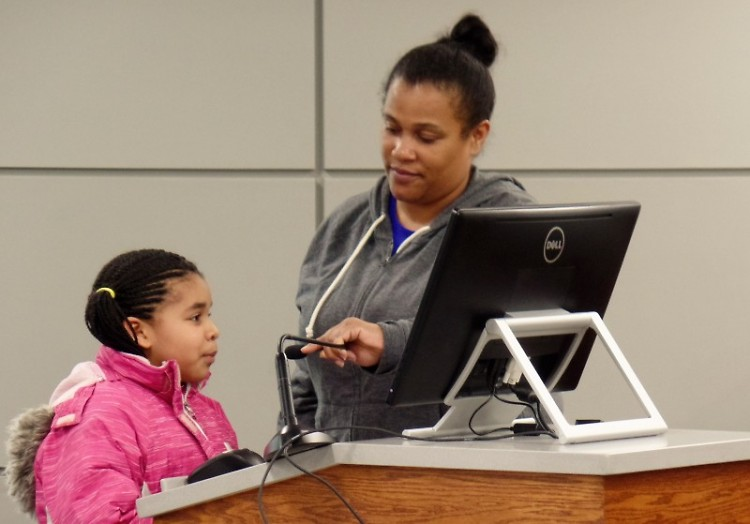 Raya Lewis (l) speaks to the Grand Rapids City Commissioners with the assistance of LaDonna Norman