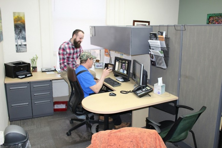 Spencer, Resource Office Coordinator, shows Zach, Dégagé patron, how to connect to the online doctor