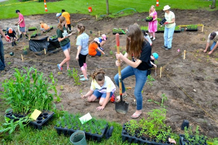 Volunteers from East Rockford Middle School partner with Michigan Trout Unlimited to plant deep-rooted native vegetation.