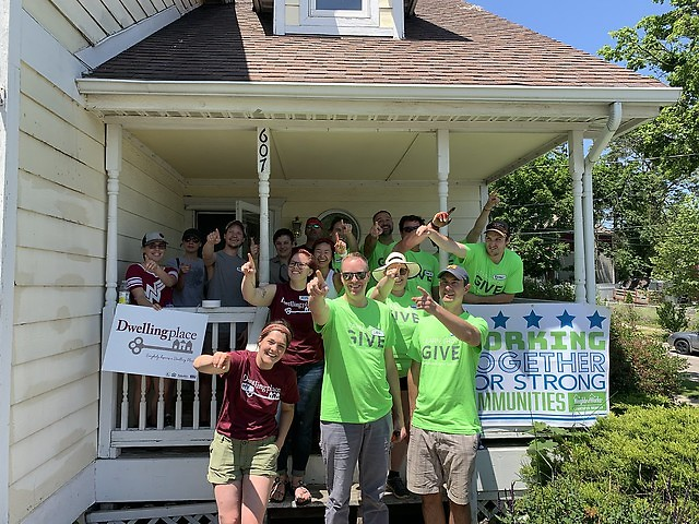 A group of volunteers from GMB Engineering and Architects celebrate after Property Days at Grandville Homes in SW GR.