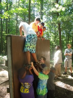 A cabin of campers taking on The Wall Challenge at Camp Tall Turf
