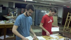 Society members Drew Damron (L) and Brian Boss (R) assemble zines.