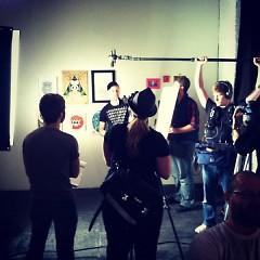 An artist speaks about their art in the Con Artist Crew gallery on Godfrey