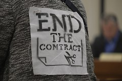 """End the Contract"" print on a GR Rapids Response to ICE member giving public comment"