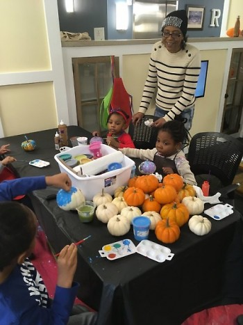 Young participants painted pumpkins to adorn their apartment buildings for the fall season