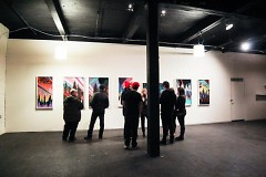 Visitors look at the artwork on display in the black and white Con Artist Crew gallery