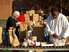 Volunteers sorting AND boxing donated items.