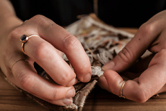 Artist Ama Wertz's hands working on tapestry photo by Melanie Jones Photography