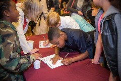 Kid authors signing books after the reading