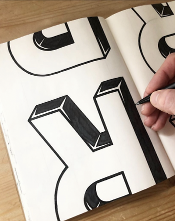 Battjes inking the letter 'R.'