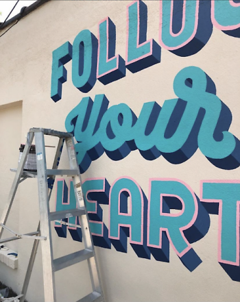 A mural in progress on the side of Five Star Realty in Grand Rapids' East Hills neighborhood.